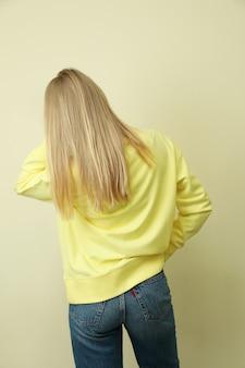 Молодая женщина в желтой кофте против бежевого