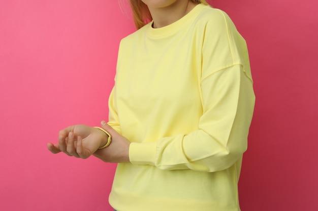 Молодая женщина в желтой кофте против розового