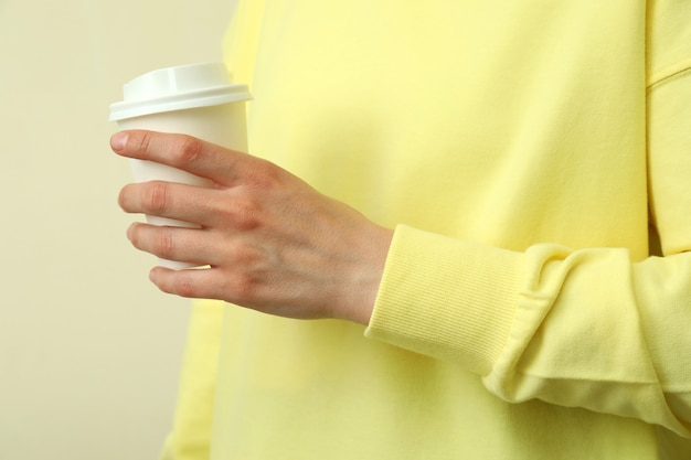 黄色のスウェットシャツの若い女性はベージュの背景に紙ガラスを保持します。