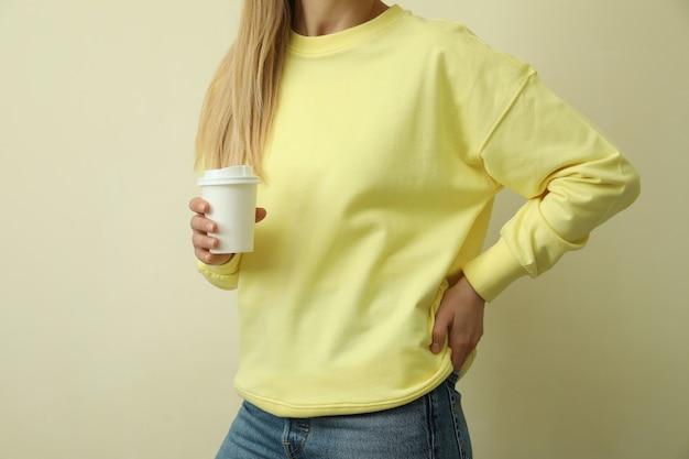 Молодая женщина в желтой толстовке держит бумажное стекло на бежевом