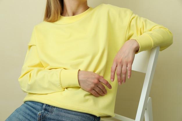 ベージュの表面に座っている黄色のスウェットシャツの若い女性