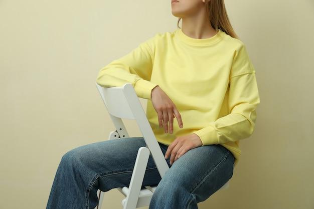 Молодая женщина в желтой толстовке сидит против бежевого