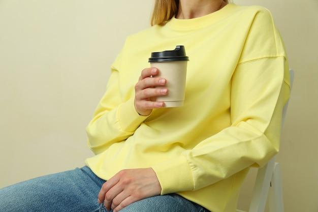 ベージュの表面に紙コップで座っている黄色のスウェットシャツの若い女性