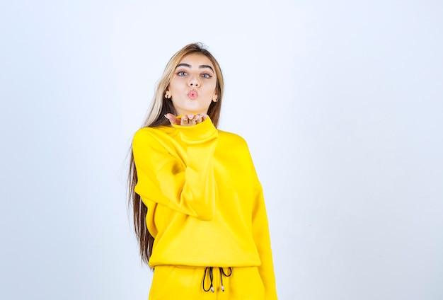 흰 벽에 키스를 불고 노란색 운동복에 젊은 여자