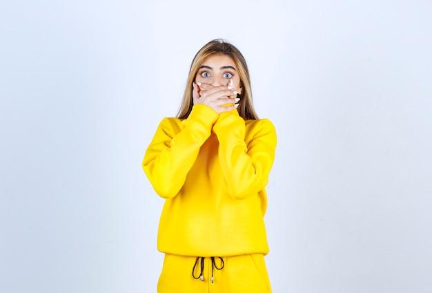 흰 벽 위에 입을 가리고 있는 노란색 운동복을 입은 젊은 여성