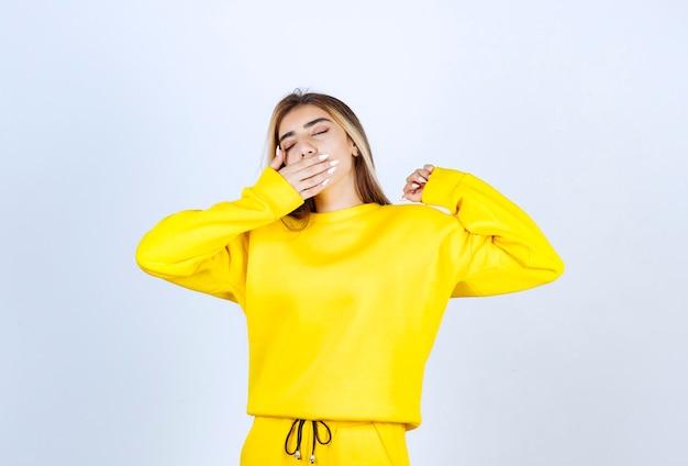 Молодая женщина в желтом спортивном костюме, чувствуя себя сонной над белой стеной