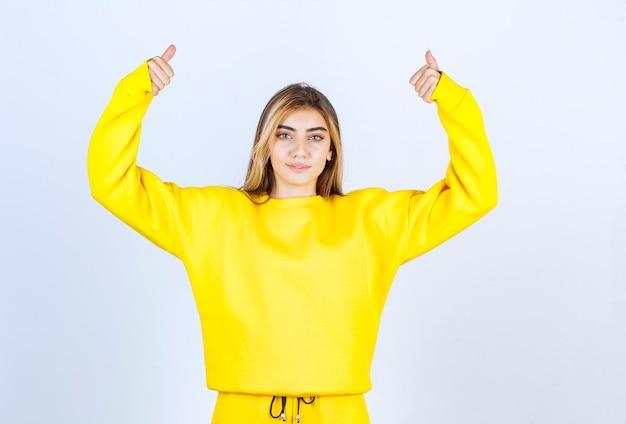 흰 벽에 엄지손가락을 포기하는 노란색 운동복을 입은 젊은 여자