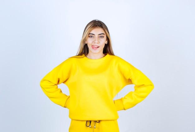 흰 벽에 카메라를 향해 포즈를 취하는 노란색 운동복을 입은 젊은 여성