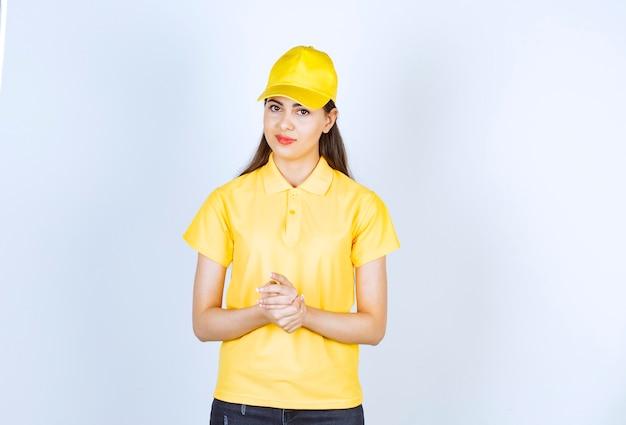 白い背景の上に立っている黄色のtシャツと帽子の若い女性。