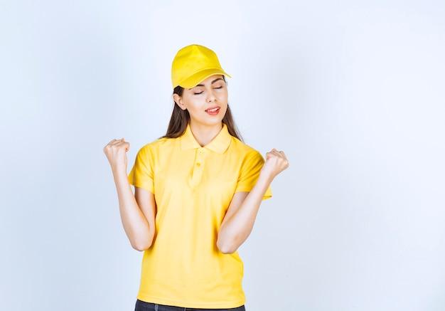 Молодая женщина в желтой футболке и кепке, стоя на белом фоне.