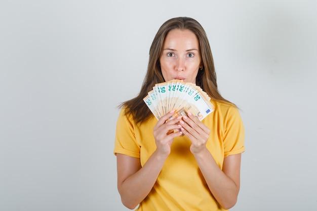 Молодая женщина в желтой футболке держит банкноты евро и смотрит внимательно