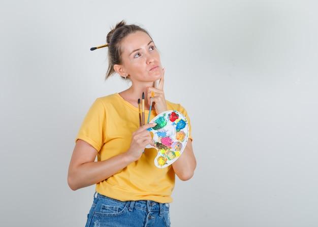 Молодая женщина в желтой футболке, джинсах смотрит вверх и держит инструменты для рисования