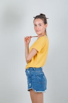 Молодая женщина в желтой футболке, джинсовых шортах смотрит в камеру с малярной кистью и выглядит весело