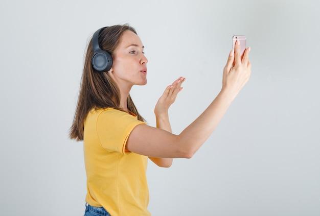 黄色のtシャツを着た若い女性、ビデオコールを介して電話でキスを送信するショートパンツ