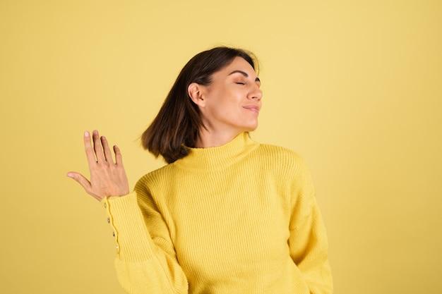 Молодая женщина в желтом теплом свитере с закрытыми глазами