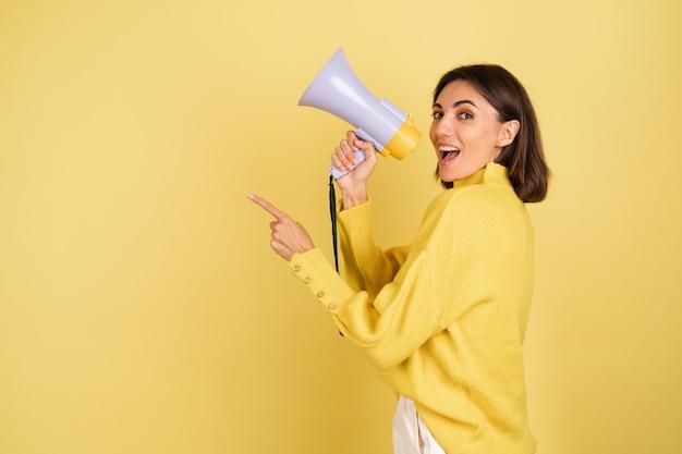 Молодая женщина в желтом теплом свитере с громкоговорителем мегафона кричит налево, указывая указательным пальцем