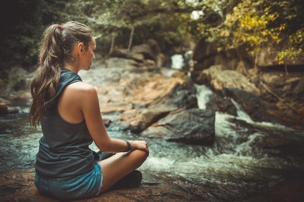 요가 포즈 폭포 근처에 앉아있는 젊은 여자