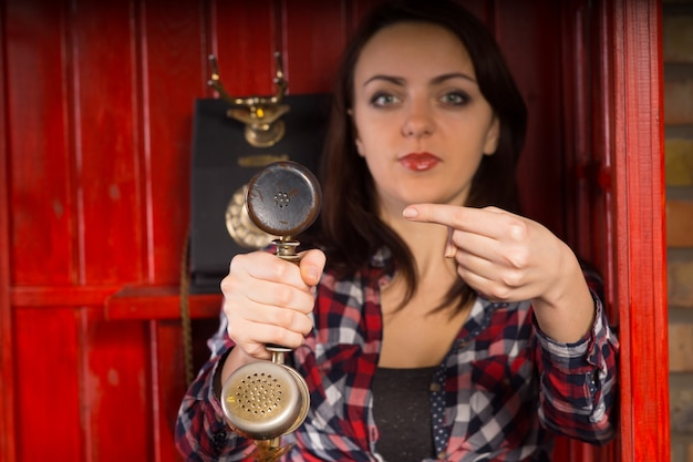 Young woman indicating an incoming phone call as she holds a vintage handset towards the viewer and points at it with her finger