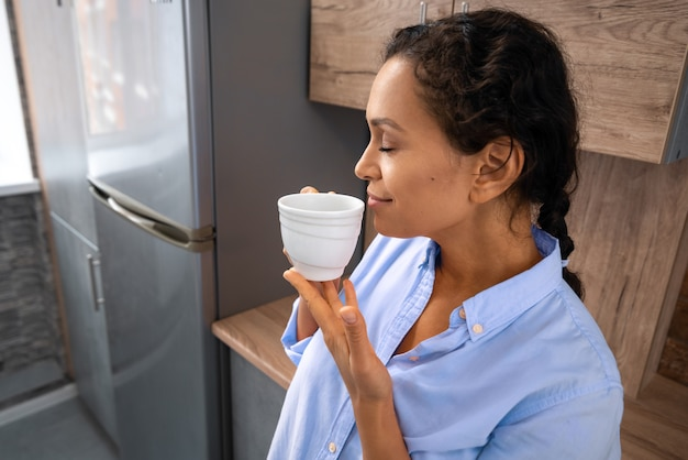 The young woman inhales the aroma of coffee from a cup while standing in the kitchen.