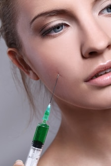 Young woman injecting for a beauty treatment