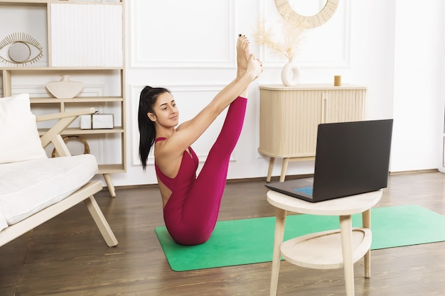 Young woman instructor conducts online yoga classes at home
