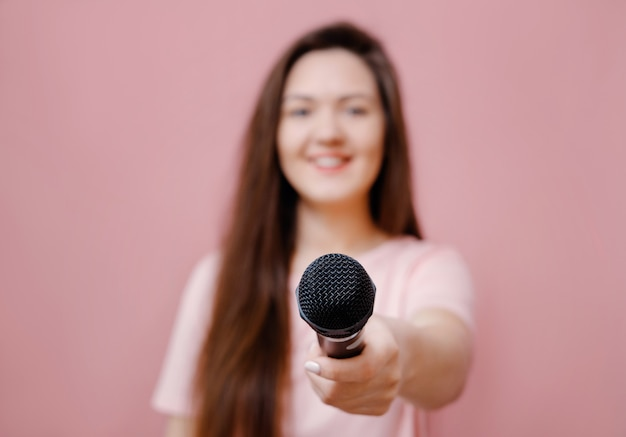 Young woman interviewer with microphone in hand