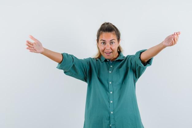 Giovane donna che invita a venire in camicetta verde e dall'aspetto amabile