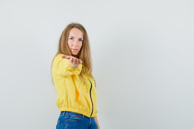 Young woman inviting to come in yellow bomber jacket and blue jean and looking serious. front view.