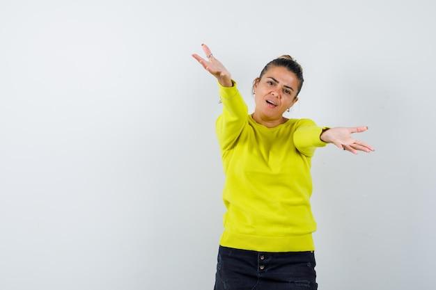 Молодая женщина приглашает прийти в желтом свитере и черных брюках и выглядит любезно