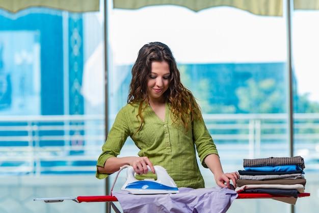 Молодая женщина гладит одежду на борту