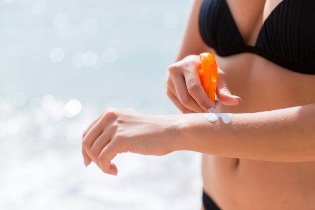 Young woman is applying protective sun cream on her hand at the beach.