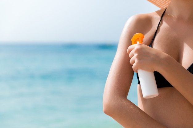 Young woman is applying protective sun cream on her shoulder at the beach.