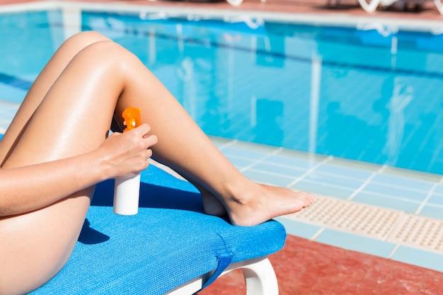 若い女性は、プールサイドの滑らかな日焼けした脚に日焼け止めクリームを塗っています。休暇中の日焼け止めファクター、コンセプト。