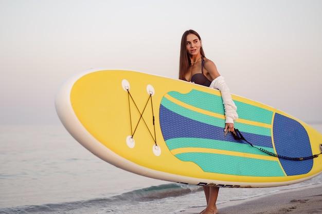 젊은 여자가 해변에서 패들 보드를 들고 있다