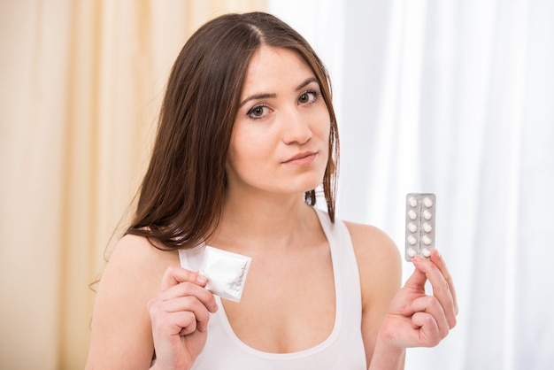 Young woman is choosing her way - condom or pills.
