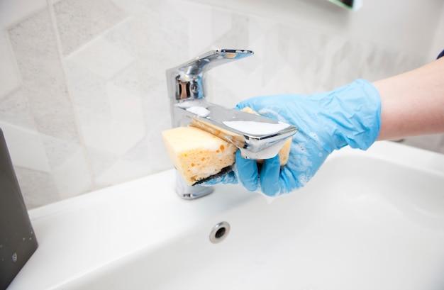 Молодая женщина моет кран в ванной