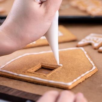 若い女性がクリスマスジンジャーブレッドクッキーを飾っています
