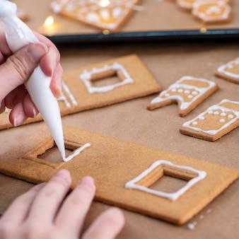 若い女性は、アイシングバッグ、クローズアップ、ライフスタイルのフロスティングトッピングで自宅でクリスマスジンジャーブレッドハウスクッキービスケットを飾っています。