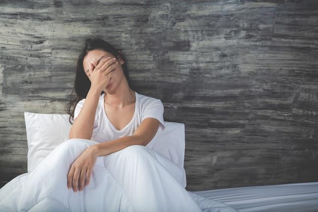 若い女性は白いベッドに落ち込んでいます