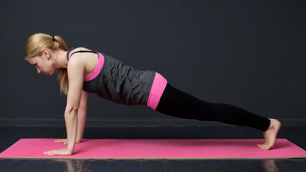 Young woman is doing push-ups on the floor