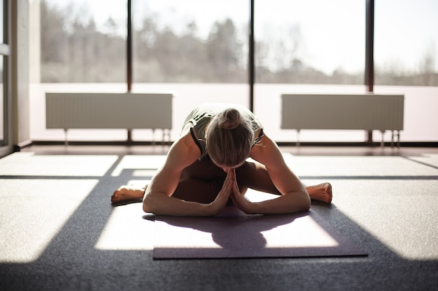 A young woman is doing yoga in the gym. a girl meditates against the background of panoramic windows in a modern yoga studio. the concept of a healthy lifestyle, place for text