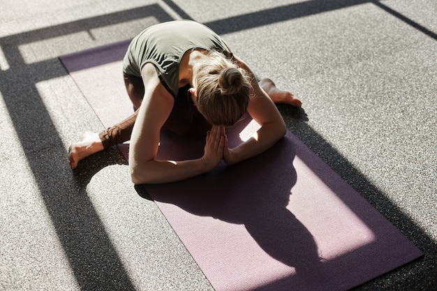 A young woman is doing yoga in the gym. a girl meditates against the background of panoramic windows in a modern yoga studio. type of supernumerary, space for text
