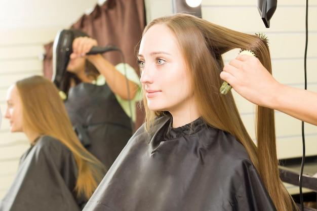 젊은 여자는 헤어 드라이어로 머리카락을 말리고 있습니다.