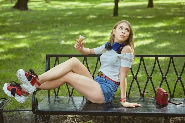 젊은 여자는 공공 공원에서 벤치에 누워있는 동안 아이스크림을 먹고있다.