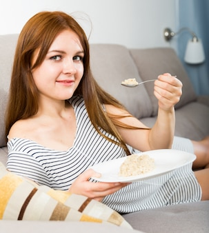 Молодая женщина ест овсяную кашу на диване