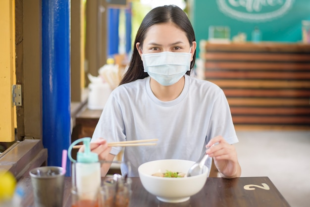 A young woman is eating thai street food , wearing face mask, new normal eating concept