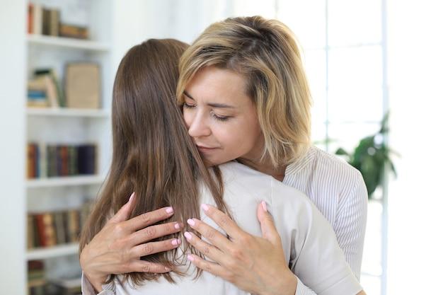 젊은 여자가 거실에서 그녀의 중년 어머니를 껴안고 있습니다.