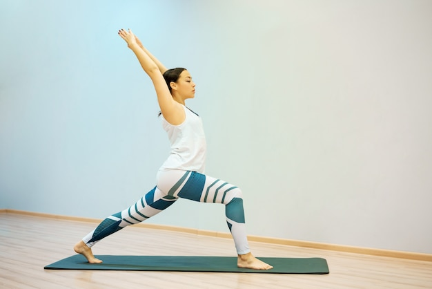 A young woman is engaged in fitness at home on the mat