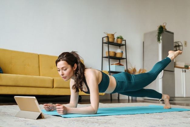 Young woman is engaged in fitness at home