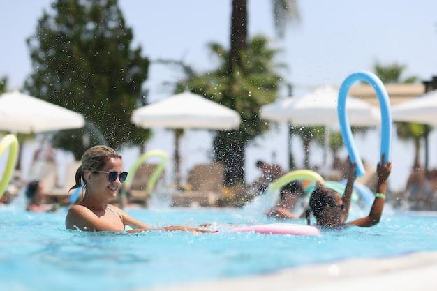 젊은 여성은 아쿠아 에어로빅 개념의 야외 수영장 혜택에서 아쿠아 에어로빅에 종사하고 있습니다